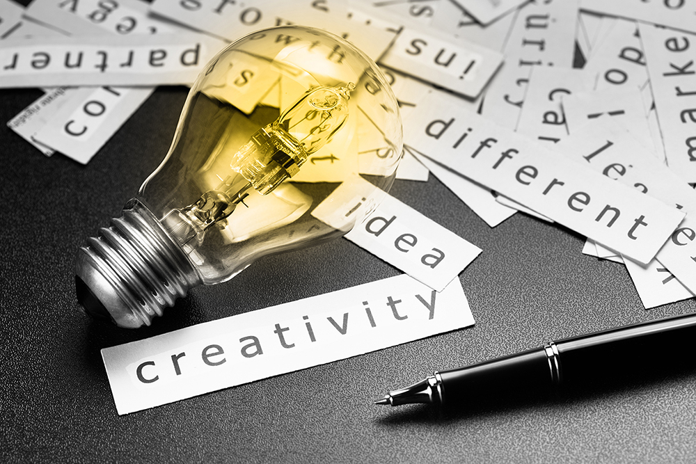 Pile of inspiration words printed in pieces of paper with light bulb and pen, closeup at Creativity word